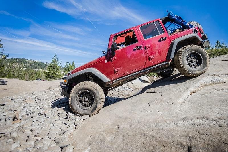 Red Jeep on granite slabs